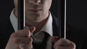 Persona criminal enojada del negocio que se coloca detrás de las barras de metal en la celda de prisión, soborno almacen de video