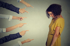 Persona culpable de la acusación Mujer triste del trastorno que mira abajo de muchos fingeres que señalan en ella detrás Imagen de archivo libre de regalías