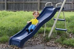 Persona del globo en la diapositiva de un niño azul en el patio trasero Fotos de archivo libres de regalías