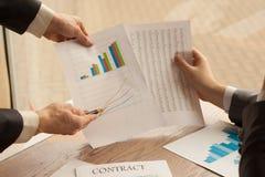 Persona del negocio que analiza las estadísticas financieras exhibidas en un sh Fotos de archivo libres de regalías