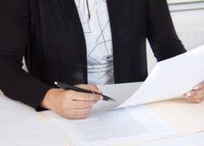 Persona del negocio que lee documentos financieros Imagenes de archivo