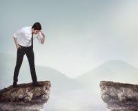 Persona del negocio que mira abajo del top del acantilado Fotografía de archivo