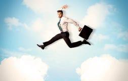Persona del negocio que salta sobre las nubes en el cielo Imágenes de archivo libres de regalías