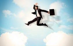 Persona del negocio que salta sobre las nubes en el cielo Foto de archivo libre de regalías