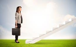 Persona del negocio que sube para arriba en la escalera blanca en naturaleza Imágenes de archivo libres de regalías