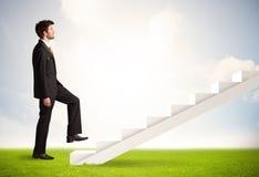 Persona del negocio que sube para arriba en la escalera blanca en naturaleza Imagen de archivo libre de regalías