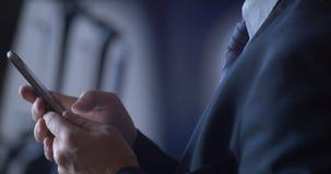 Persona del negocio que viaja en el avión de aire que comprueba smartphone móvil de la célula metrajes