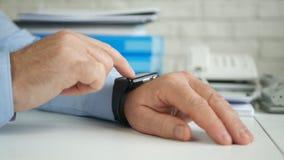 Persona di affari Access Smartwatch Technology ed inviare un messaggio facendo uso di Internet fotografie stock libere da diritti