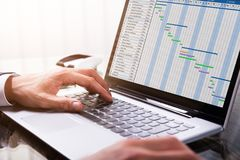Persona di affari Analyzing Gantt Chart sul computer portatile fotografie stock libere da diritti