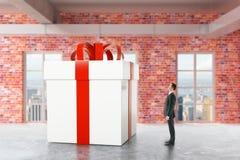 Persona di affari che esamina regalo enorme illustrazione di stock