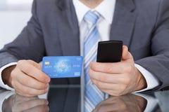Persona di affari che usando la carta del telefono Immagine Stock