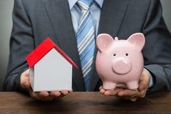 Persona di affari con il modello della casa e del porcellino salvadanaio Fotografia Stock Libera da Diritti