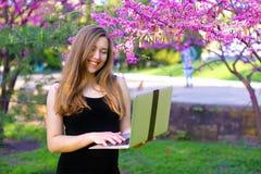 Persona di affari femminile che utilizza computer portatile nel fondo di fioritura Fotografia Stock