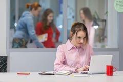 Persona di affari femminile sveglia laboriosa sul computer bianco Immagine Stock