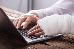 Persona di affari With Hand Injury facendo uso del computer portatile fotografia stock libera da diritti