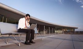 Persona di affari occupata sul telefono e sul computer portatile. Fotografia Stock
