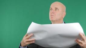Persona di affari Reading un piano della costruzione con lo schermo verde nel fondo immagine stock