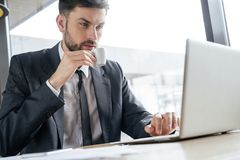 Persona di affari su pranzo di lavoro al ristorante che si siede vicino al computer portatile bevente di lettura rapida del caffè fotografie stock libere da diritti