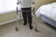 Persona di handicap che uning un camminatore per diventare mobile e indipendente immagini stock