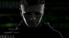 Persona di sesso maschile nella maschera che ruba i dati personali da base di dati online, crimine cyber stock footage