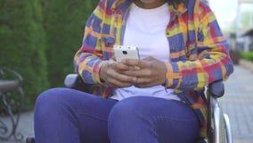 Persona discapacitada de las mujeres negras de las manos en un cierre de la silla de ruedas para arriba usando un smartphone almacen de video