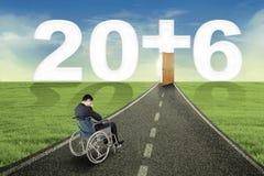 Persona discapacitada en el camino con los números 2016 Fotografía de archivo