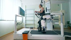 Persona discapacitada en un equipo médico robótico moderno de la recuperación Robusteza médica almacen de video