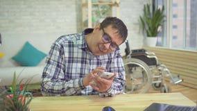 Persona discapacitada masculina adulta que usa el teléfono móvil metrajes