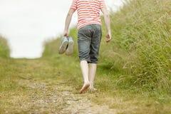 Persona en camisa rayada que camina descalzo en rastro Imagen de archivo libre de regalías