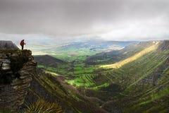 Persona en el acantilado de la montaña Fotos de archivo