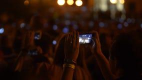 Persona en la muchedumbre que hace el vídeo y las fotos con los fuegos artificiales en el smartphone almacen de video
