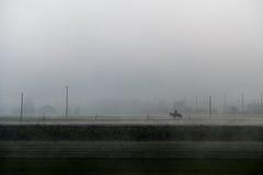Persona en un caballo que pasa a través de la niebla Foto de archivo