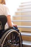 Persona en una silla de ruedas delante de una escalera Imagen de archivo