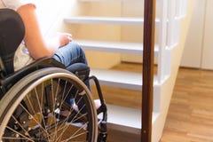 Persona en una silla de ruedas delante de una escalera Imágenes de archivo libres de regalías