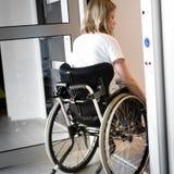 Persona en una silla de ruedas que entra en un elevador Imagenes de archivo