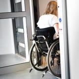 Persona en una silla de ruedas que entra en un elevador Imágenes de archivo libres de regalías