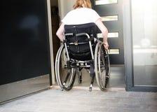 Persona en una silla de ruedas que se mueve sobre un umbral bajo Imagenes de archivo