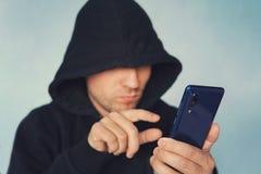Persona encapuchada irreconocible anónima que usa el teléfono móvil, el hurto de identidad y el concepto del crimen de la tecnolo foto de archivo libre de regalías