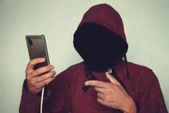Persona encapuchada irreconocible anónima que usa el teléfono móvil, el hurto de identidad y el concepto del crimen de la tecnolo imágenes de archivo libres de regalías