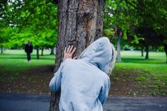 Persona encapuchada que oculta detrás de un árbol Imágenes de archivo libres de regalías