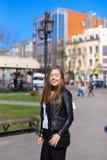 Persona femenina agradable que camina en ciudad y chaqueta de cuero que lleva Fotos de archivo