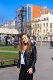 Persona femenina alegre que camina en ciudad y chaqueta de cuero que lleva Foto de archivo