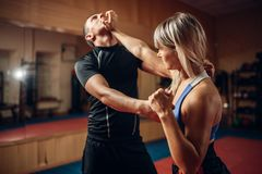 Persona femenina en entrenamiento de la autodefensa con el instructor fotografía de archivo