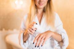 Persona femenina en la albornoz, skincare en cuarto de baño fotografía de archivo