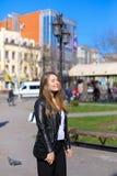 Persona femenina feliz que camina en ciudad y chaqueta de cuero que lleva Imagen de archivo
