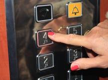 Persona femenina que empuja el botón del elevador Fotos de archivo libres de regalías