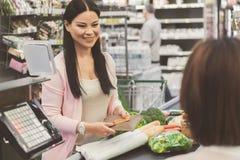 Persona femenina sonriente alegre que va a pagar mercancías Imagen de archivo