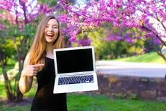 Persona femminile allegra che mostra computer portatile moderno con il fondo di fioritura del parco Fotografia Stock