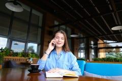 Persona femminile che riposa al caffè con il taccuino e la tazza di caffè, parlanti dallo smartphone Fotografie Stock Libere da Diritti