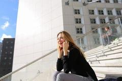 Persona femminile che si siede sulle scale e che parla dallo smartphone Immagini Stock Libere da Diritti